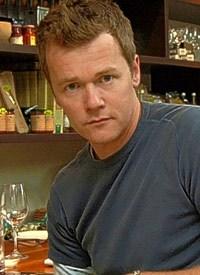 Arthur Potts Dawson in casual clothes against a restaurant backdrop