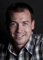 Dave Finkle head shot smiling to camera in a plaid shirt