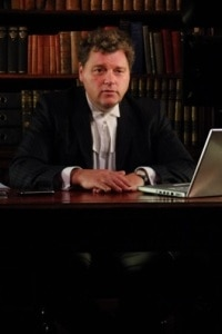 Criminal Barrister Gary Bell QC sits at his desk in his chambers for this photo wearing his QC robes.