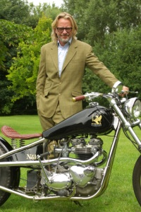 Henry Cole standing next to is Gladstone motorbike dressed in tweed