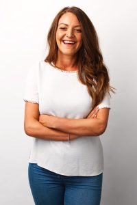 Kirsty Henshaw smiling to the camera in jeans and a white t shirt