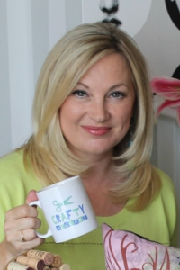 Wendy Turner Webster looking stunning in lime green and sipping out of a Crafty Beggars Mug on Set at Create and Craft
