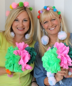 Crafty Beggars smiling to camera and both wearing pompoms in their hair and holding larger ones in their hands
