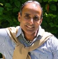 Reza Mahammad smiling at the camera in a striped shirt